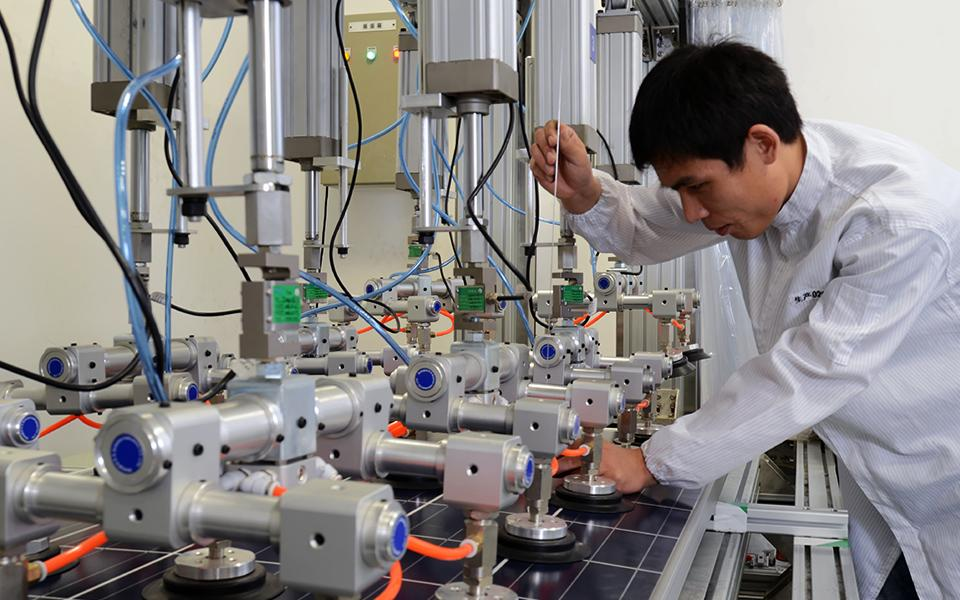 Factory worker with equipment working on solar panel