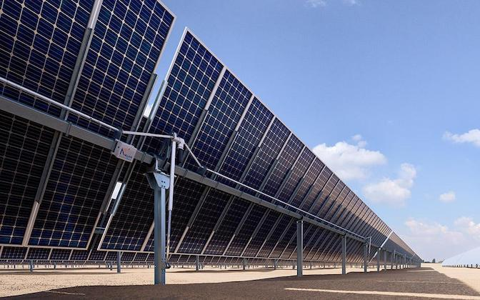 View from below a solar panel installation showing groundmounts with trackers and blue sky in background